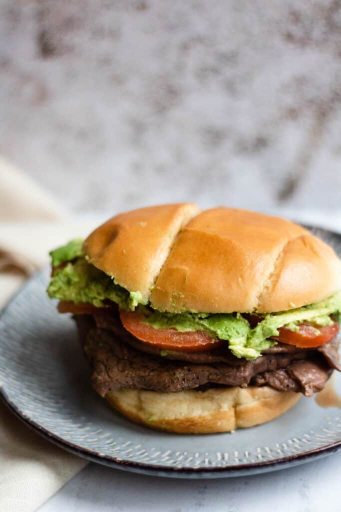 Churrasco steak Sandwich on a plate with tomatoes and avocado