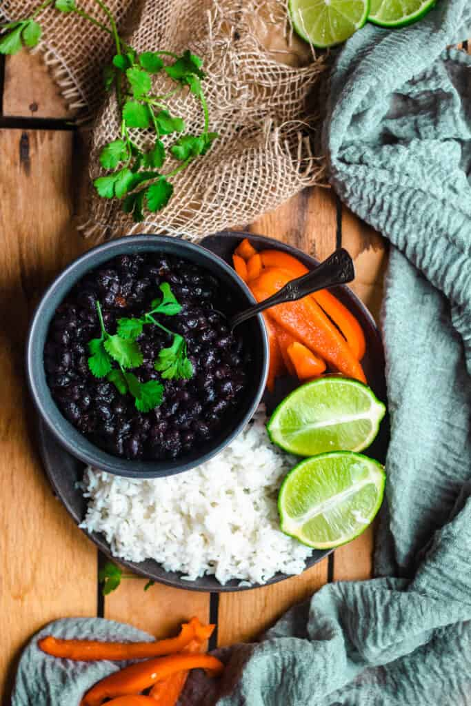 Overhead view of Cuban black beans with white rice, lime halves, and red pepper