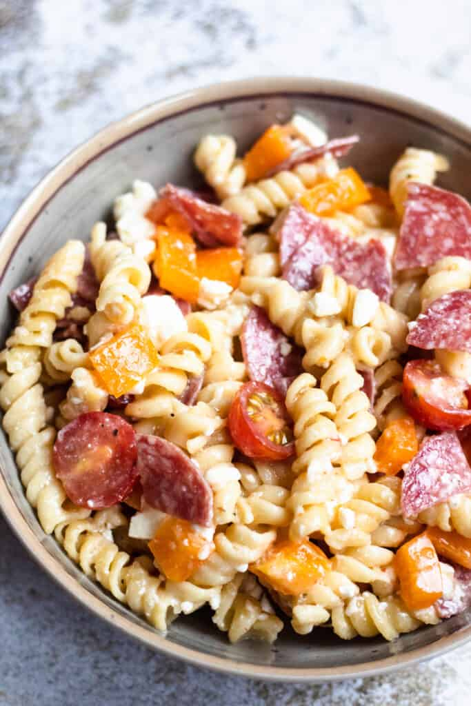 Overhead view of easy pasta salad on a concrete background. Rotini pasta with peppers and salami