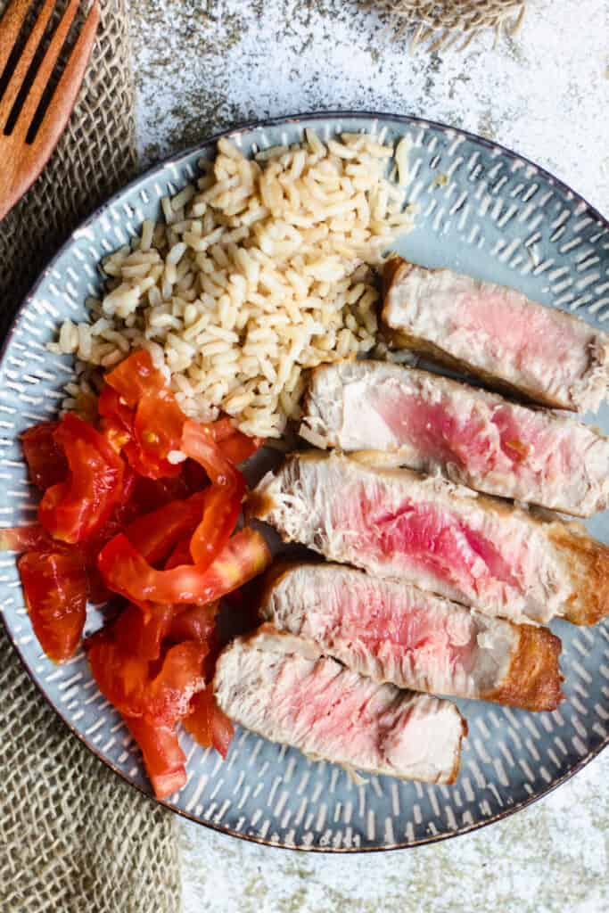 Sliced Fried tuna with rice and tomatoes as a side