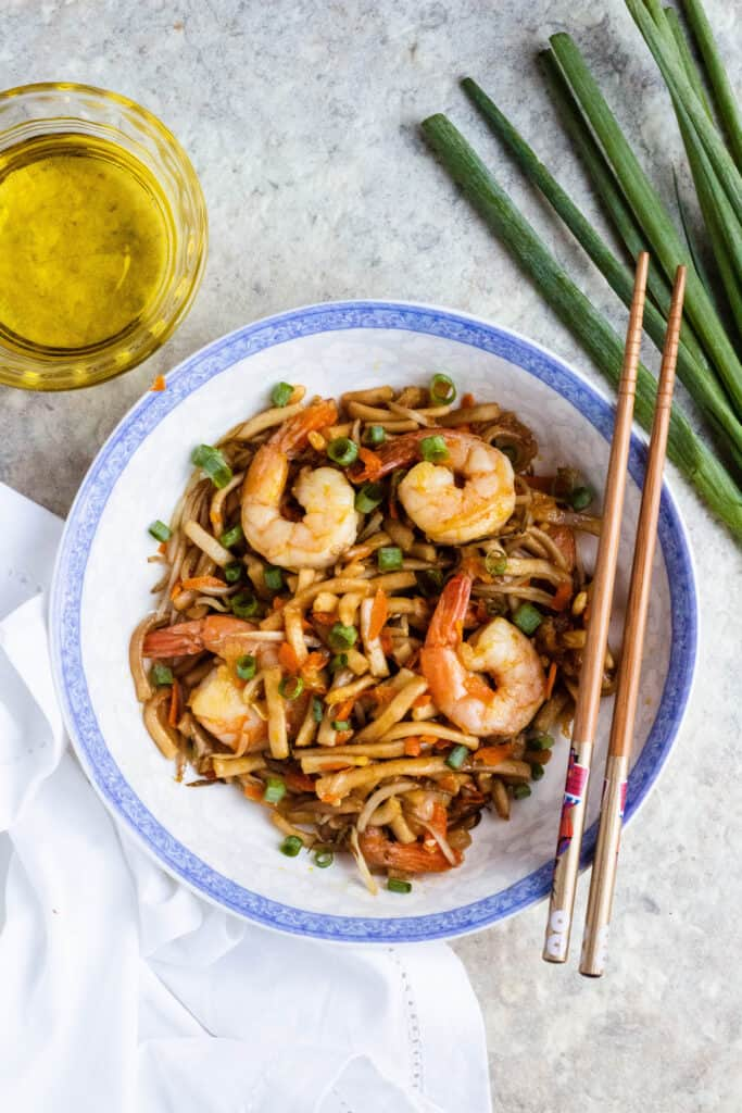 Overhead view of shrimp stir fry with chopsticks and green onions
