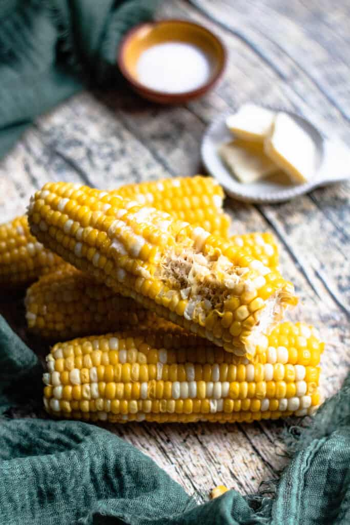 Corn on the cobs stacked with a bite out of it