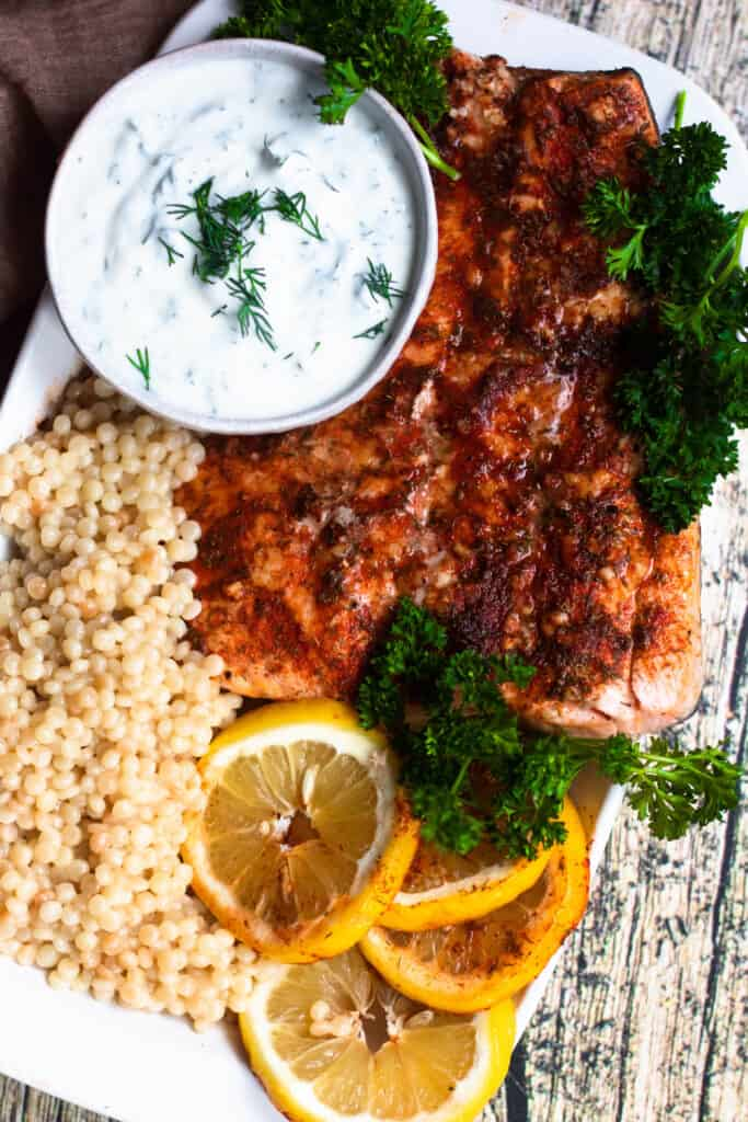 Close up of Instant Pot Salmon with paprika, couscous, parlsey, and lemon slices