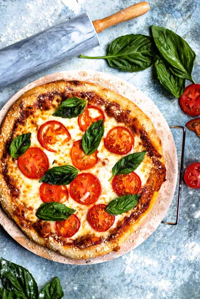 Overhead view of margerita pizza with basil leaves and tomatoes