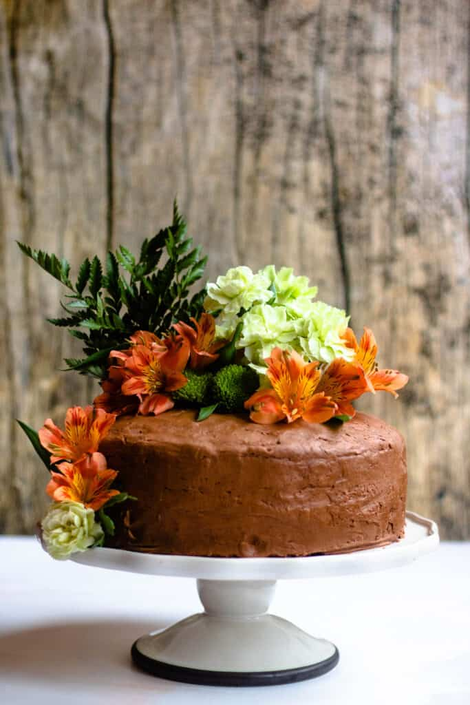 front view of chocolate mayonnaise cake decorated with orange and green flowers