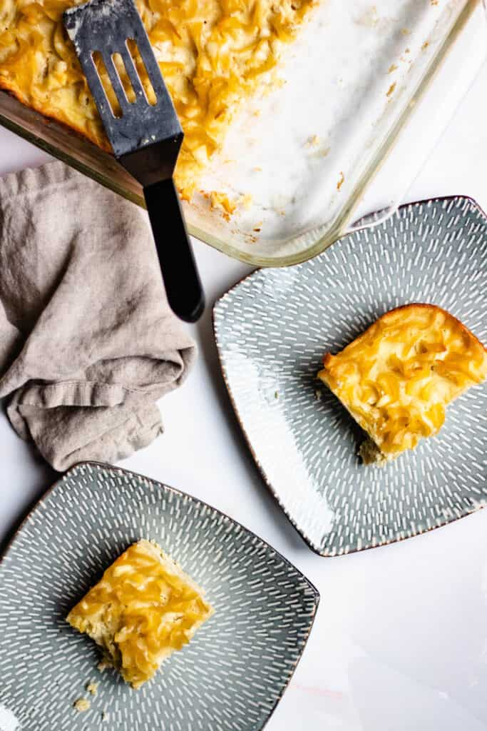 Overhead view of 2 plates with a tray of kugel in the background