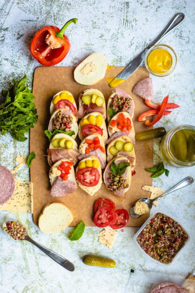 Overhead view of open faced sandwiches surrounded by utensils and ingredients