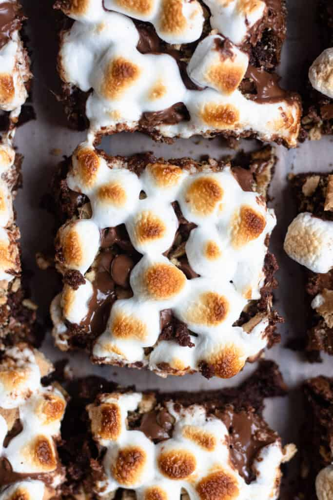 Overhead close up shot of brownies with toasted marshmallows on top