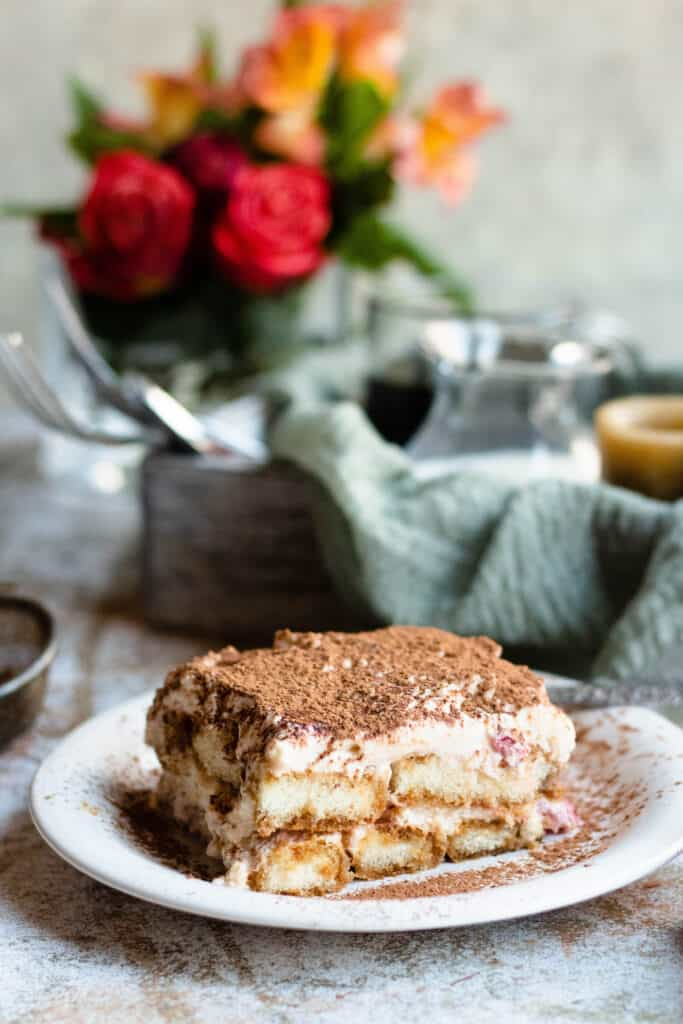 Front view of Strawberry Tiramisu with a serving platter in the background