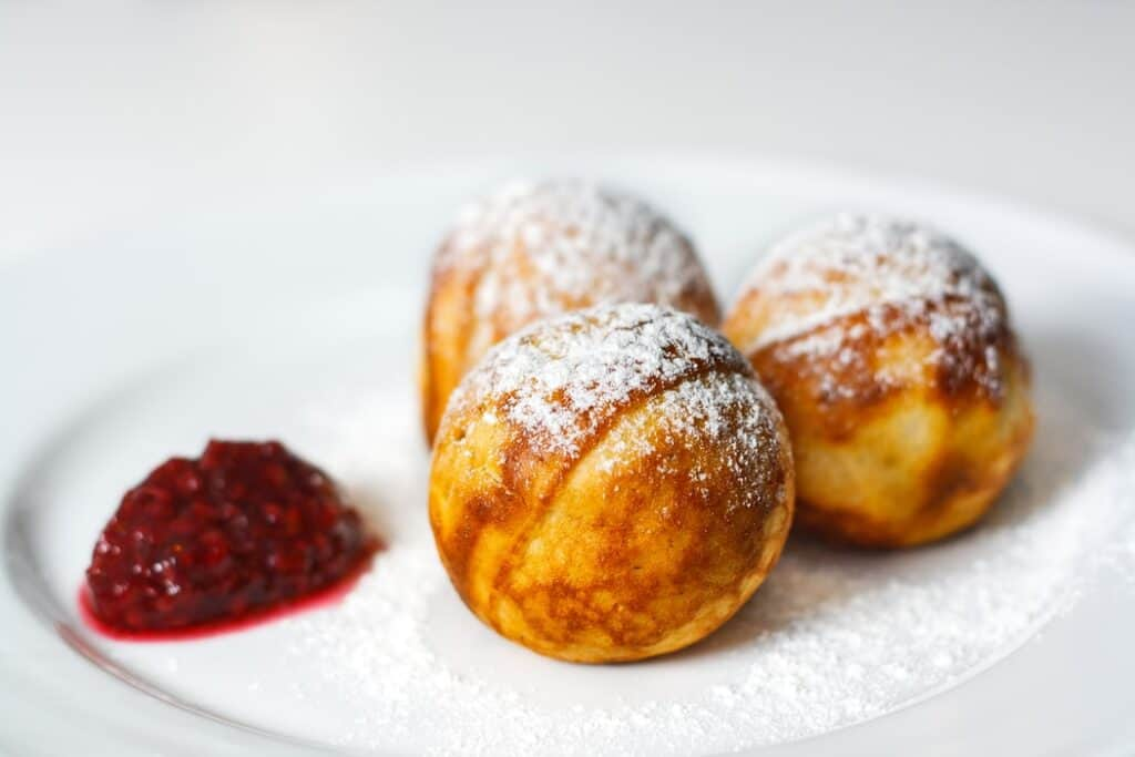 Danish dessert with powdered sugar and jam on the side