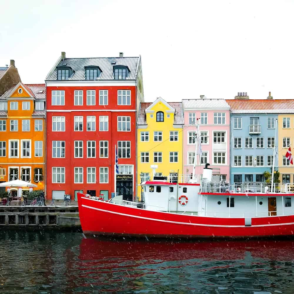 Brightly colored homes behind a boat in the water
