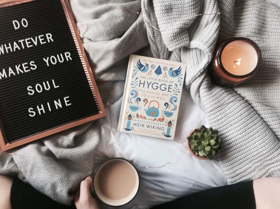 Hygge flatlay with candles, blankets, and hygge book