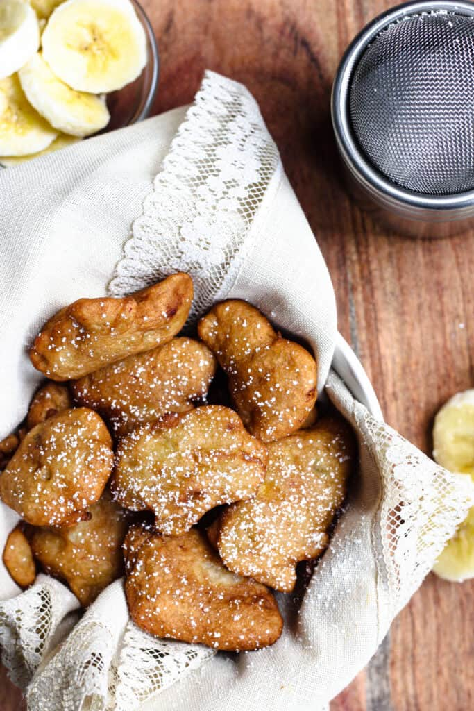 Fritters with powdered sugar in a bowl with a linen