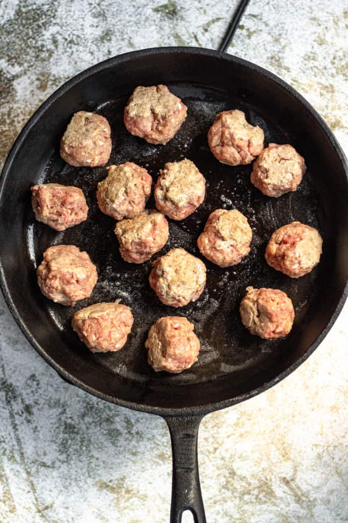 Meatballs cooking in a cast iron skillet