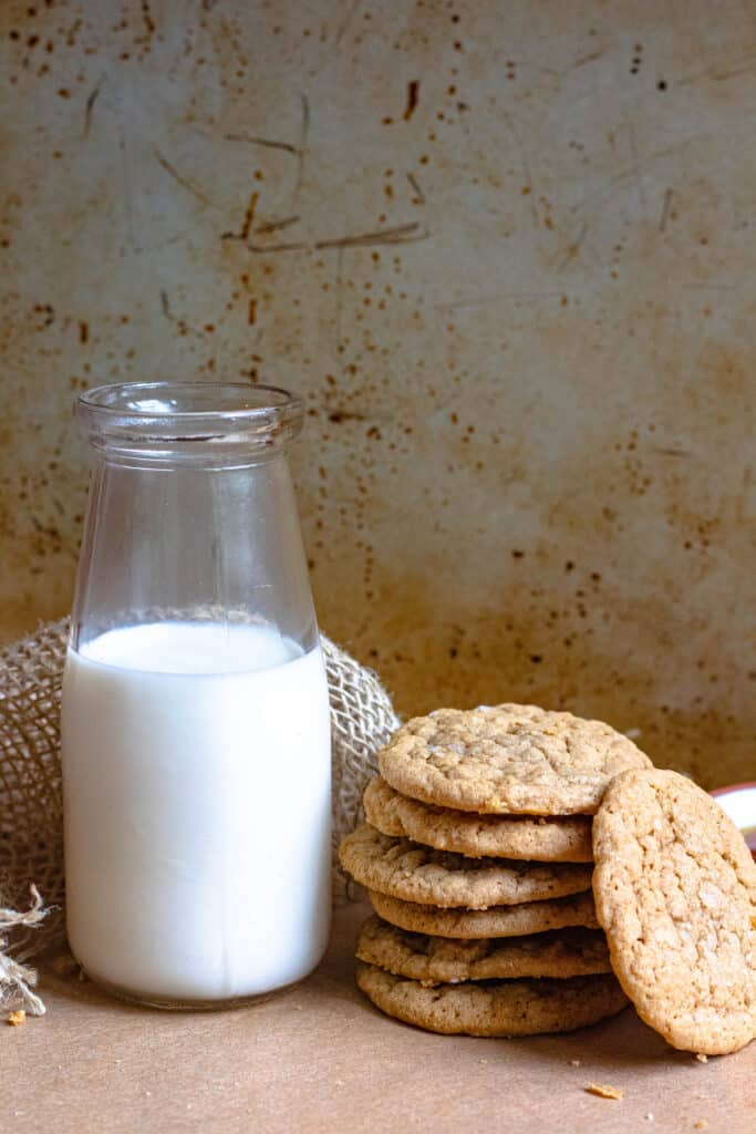 Stacked cookies next to a jar of milk