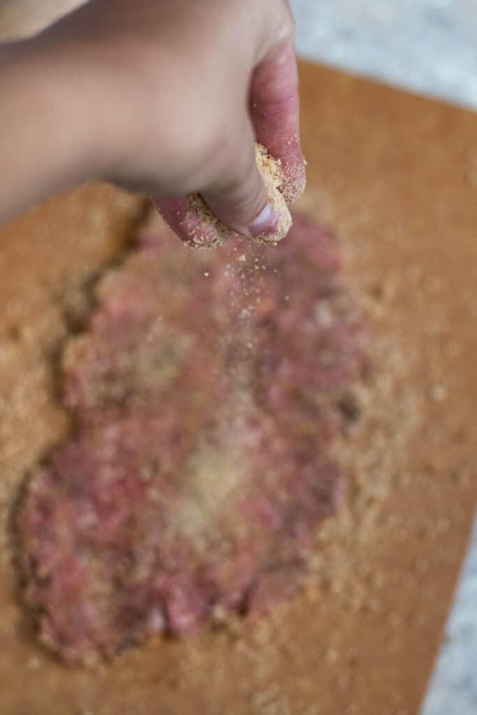 Sprinkling extra breadcrumbs on beef patties