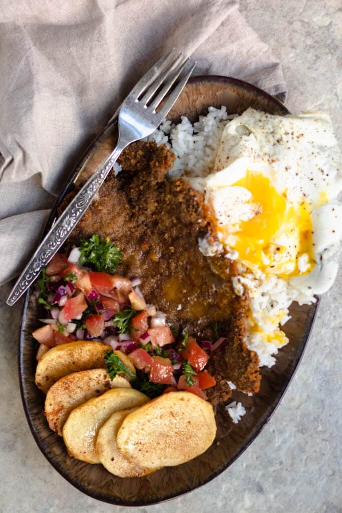 silpancho with potatoes, eggs, salsa, beef patties, etc