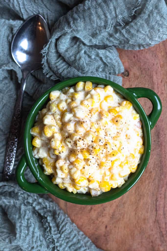 Creamed corn in a green dish with a spoon and napkin next to it. Topped with black pepper