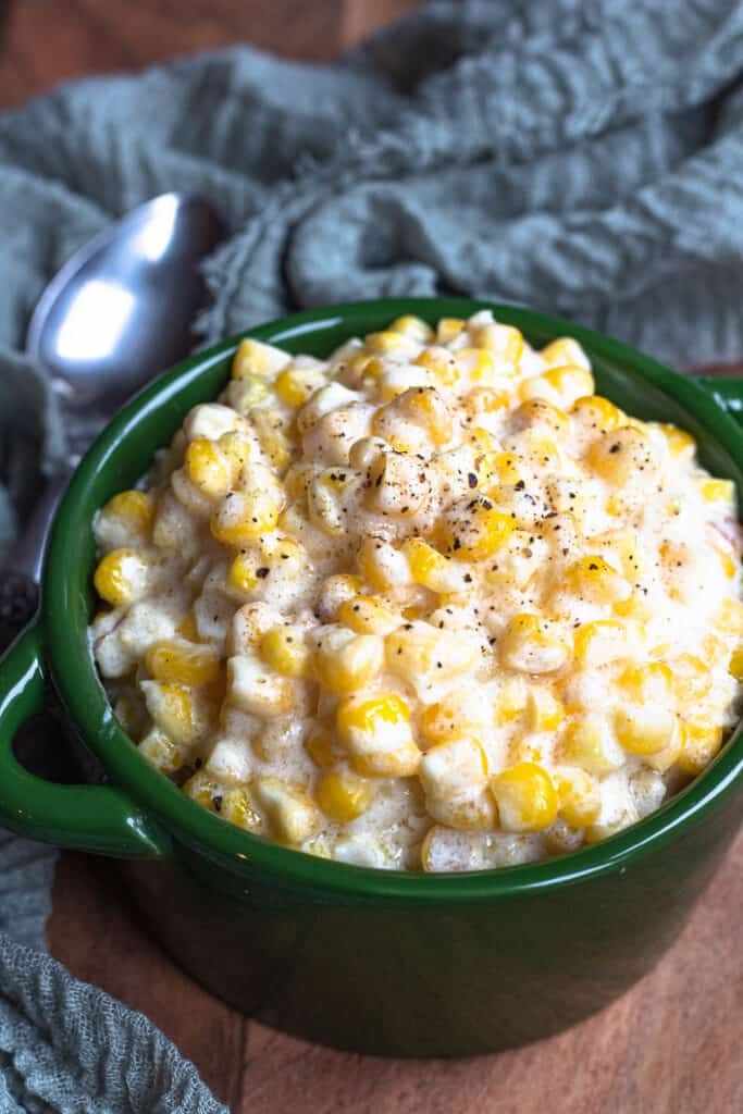 Homemade Creamed Corn topped with pepper in a green pot and a spoon behind it