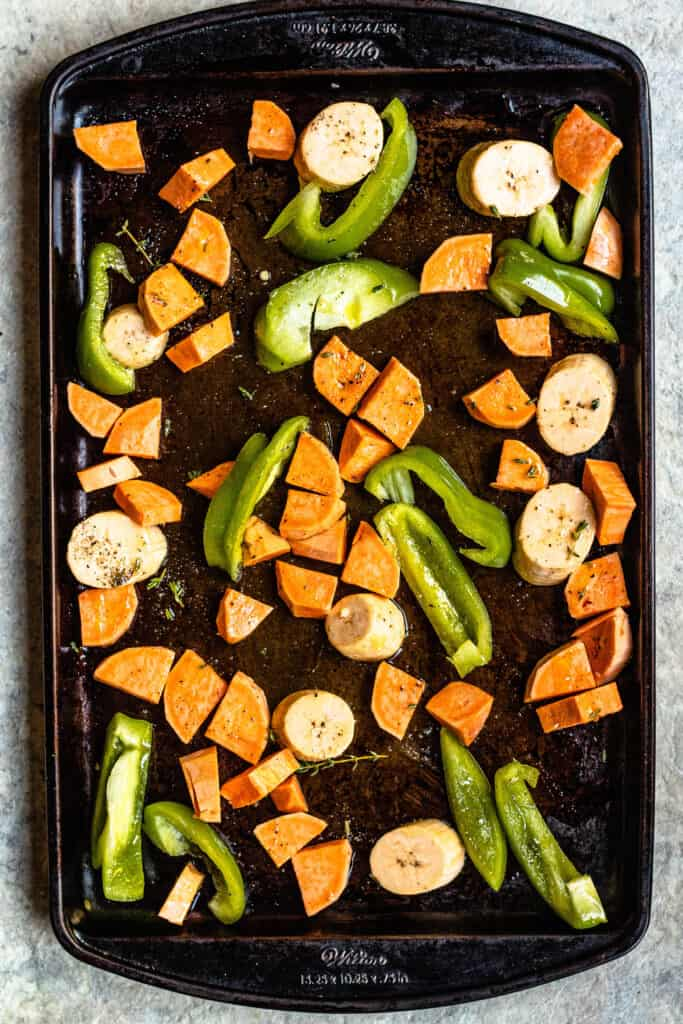 A tray of raw vegetables (plantains, sweet potatoes, and green peppers) waiting to be roasted