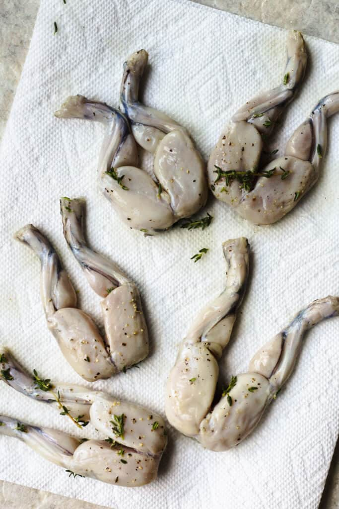 Raw frog legs covered in marinade sitting on a paper towel