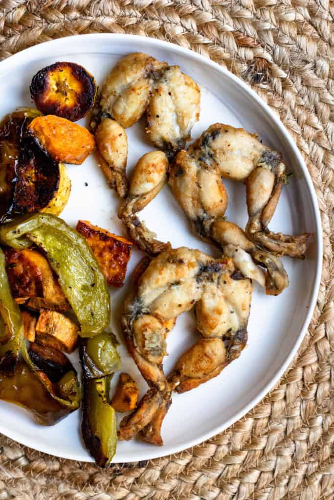 A plate of 3 frog legs with peppers and plantains on the plate with them