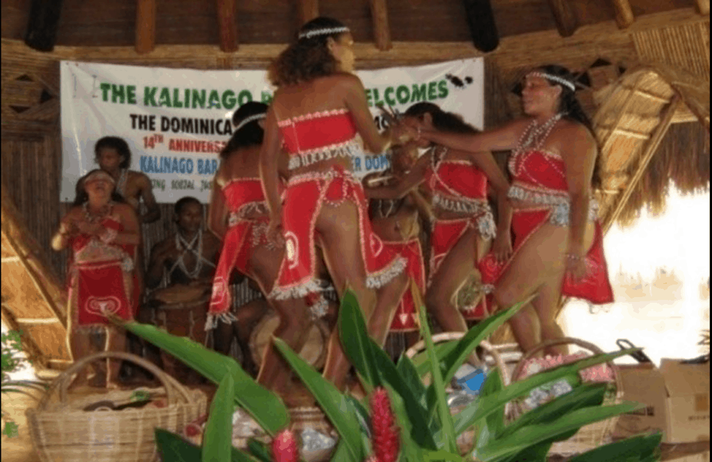Kalinago people dancing on a stage in red costumes