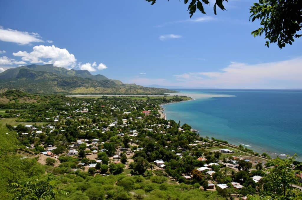 coastline of East Timor with houses and mountains in the distance.