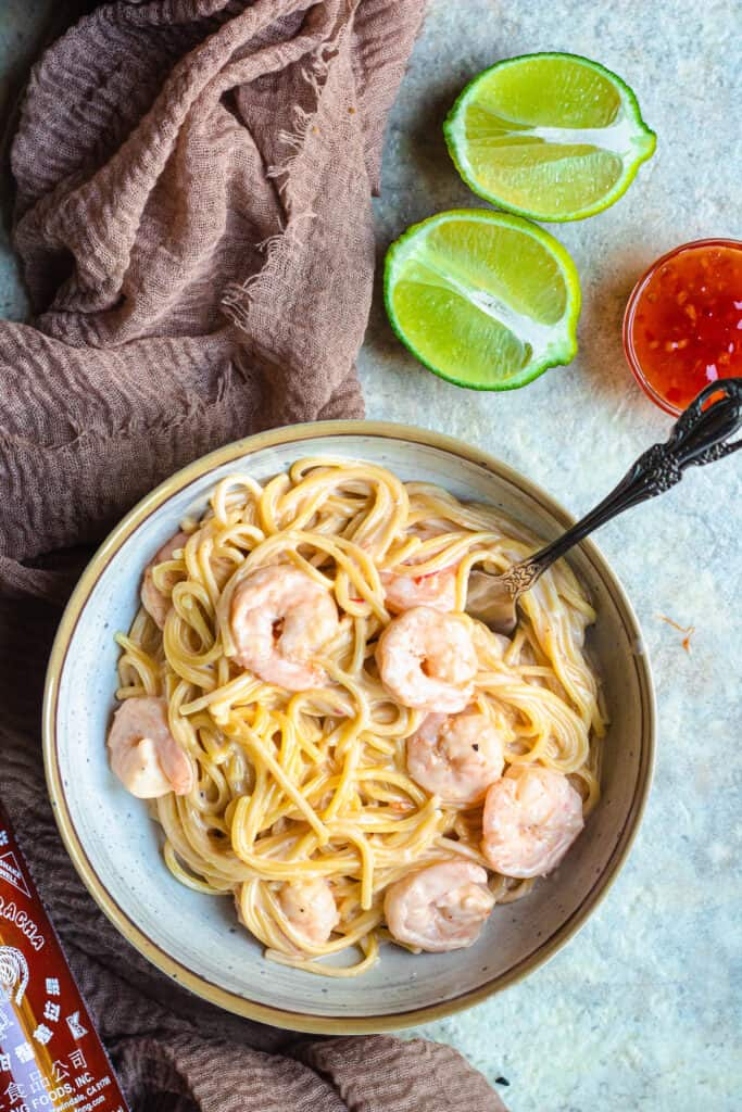 bowl of bang bang shrimp pasta with lime halves and thai chili sauce