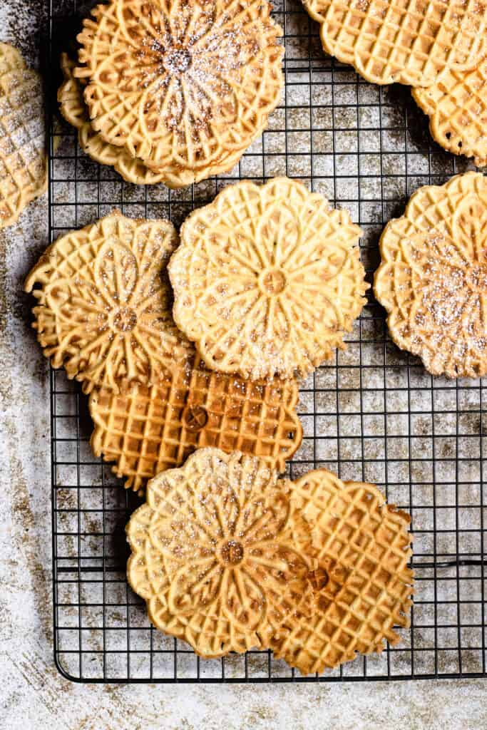 Overhead view of pizzelle spread out on a cooling wrack