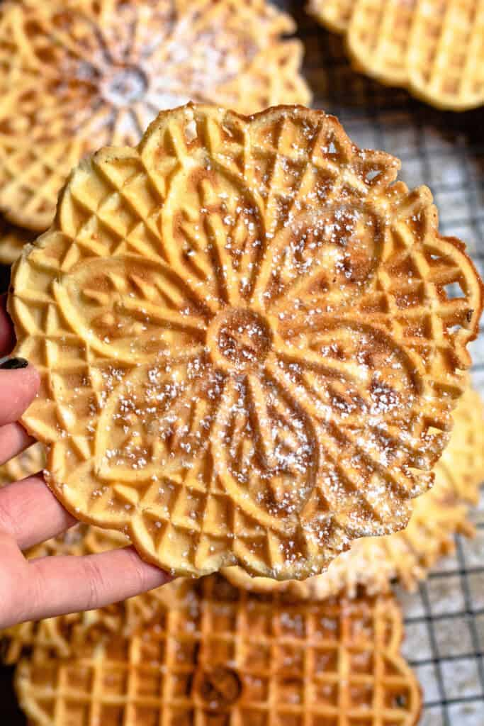hand holding up a close up of pizzelle