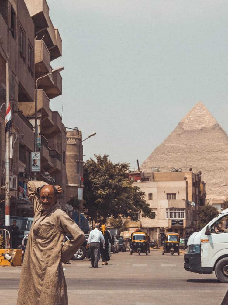 Man posing in front of the pyramids in Cairo