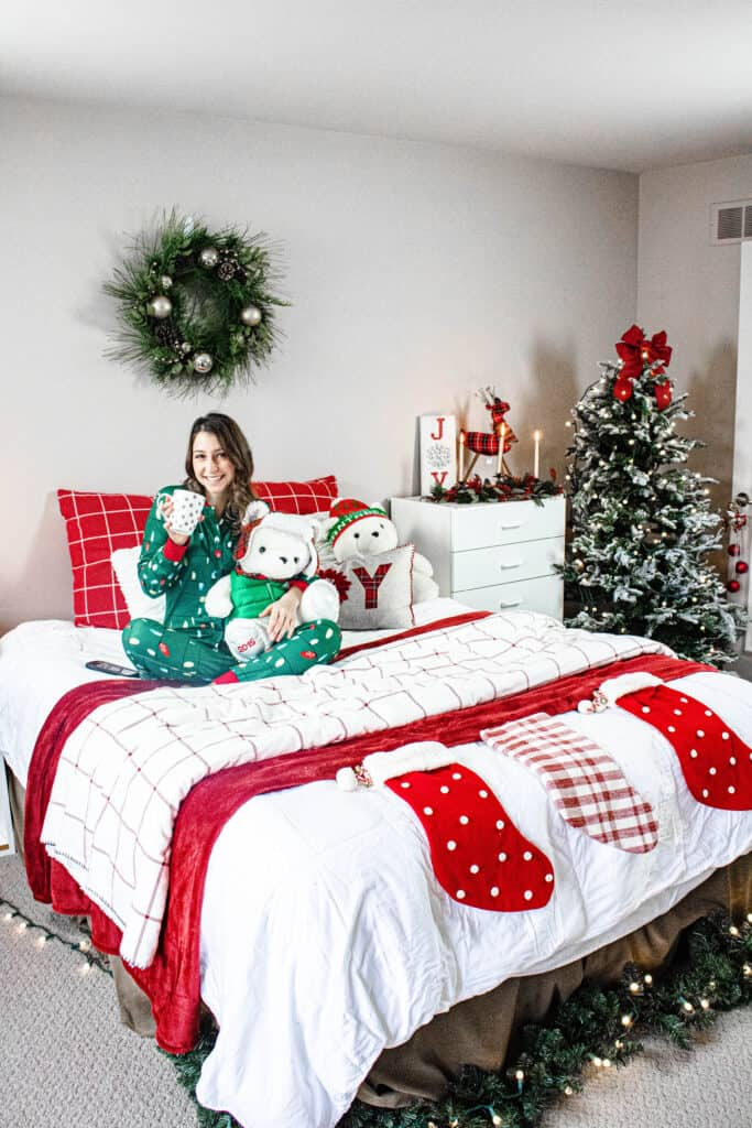 Alexandria holding a bear and a cup of coffee in a room decorated for Christmas