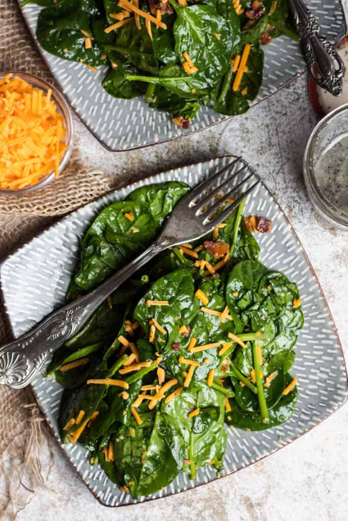 plate of spinach salad with bacon and cheese