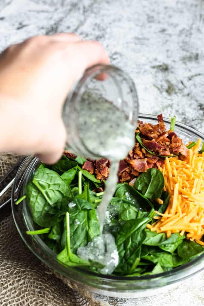 hand pouring poppyseed dressing on spinach salad with bacon and cheese