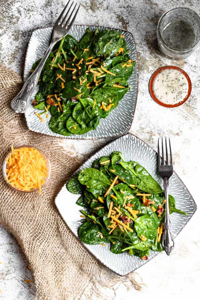 two plates of spinach salad with bacon and poppyseed dressing
