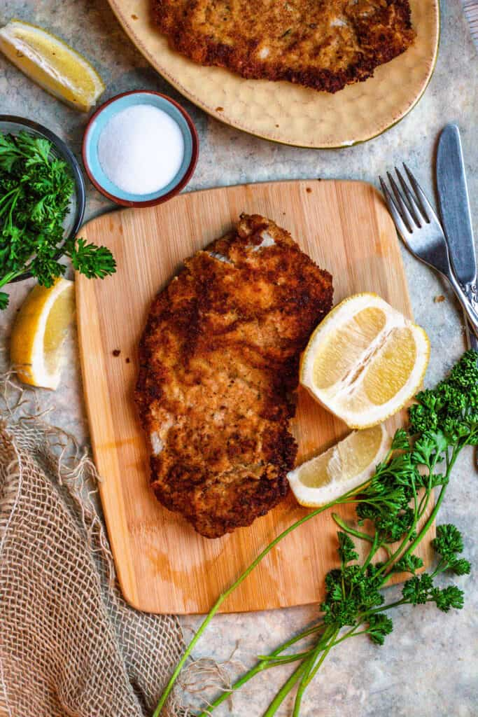 Cutting board with wiener schnitzel and slices of lemon and parsley