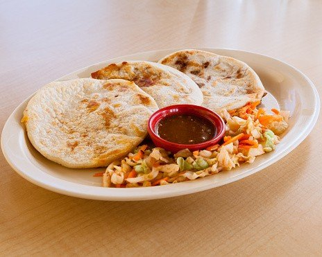 Three pupusas served with fried veggies on a white plate.