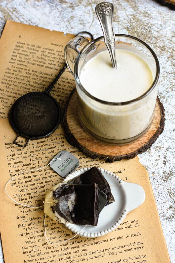 cup of butter tea with tea bags, a strainer, and yellowed book pages