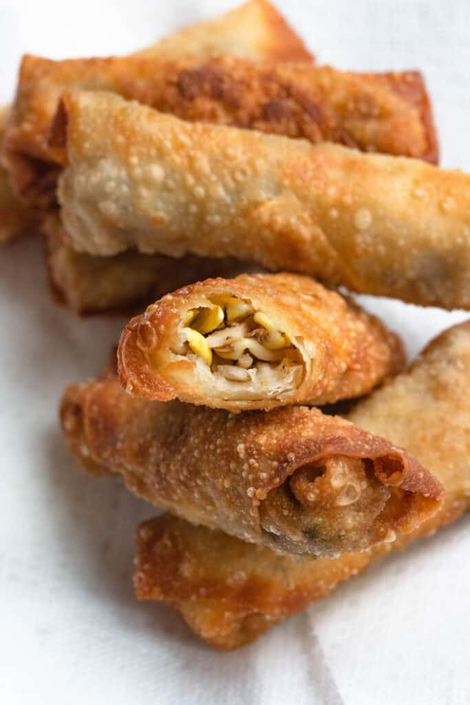 Egg rolls piled on a white paper towel with a bite out of one