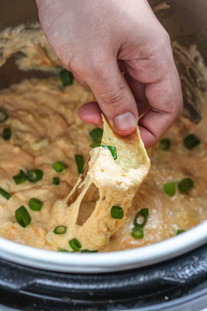 Hand dipping a tortilla chip in hot artichoke dip with scallions