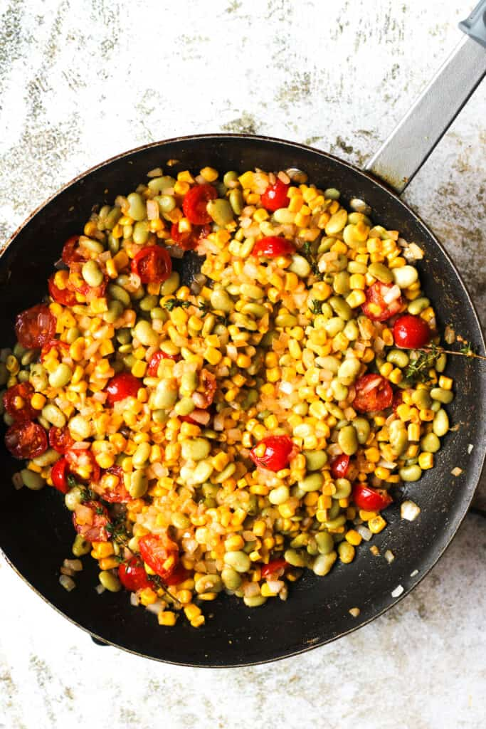 Frying pan full of cooked succotash