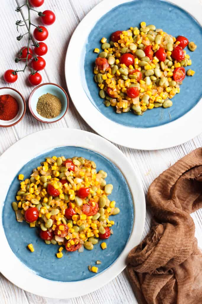 2 plates of succotash with tomatoes on a vine and 2 bowls of spices