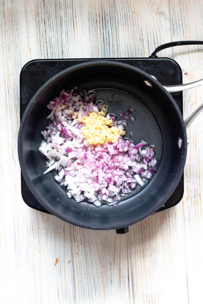 red onions and garlic cooking in a pot