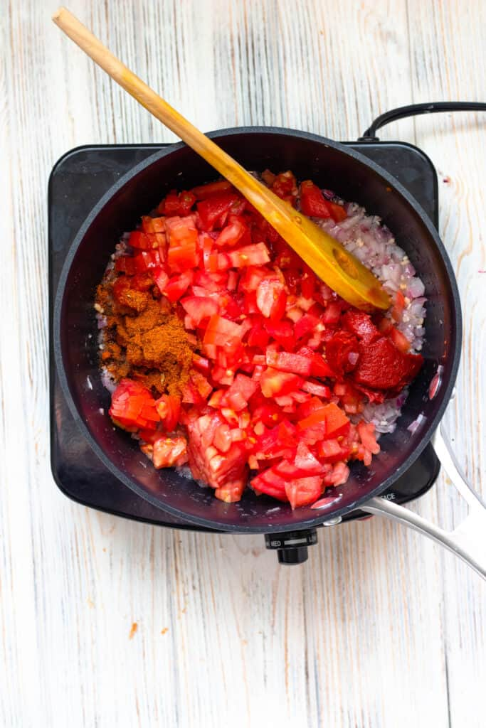Tomatoes, berbere, red onions, and tomato paste in a pot to cook