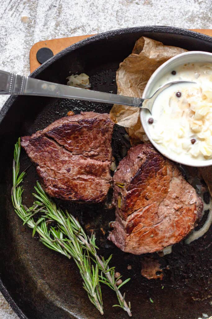 Steak in Cast iron skillet with rosemary and cream sauce next to it
