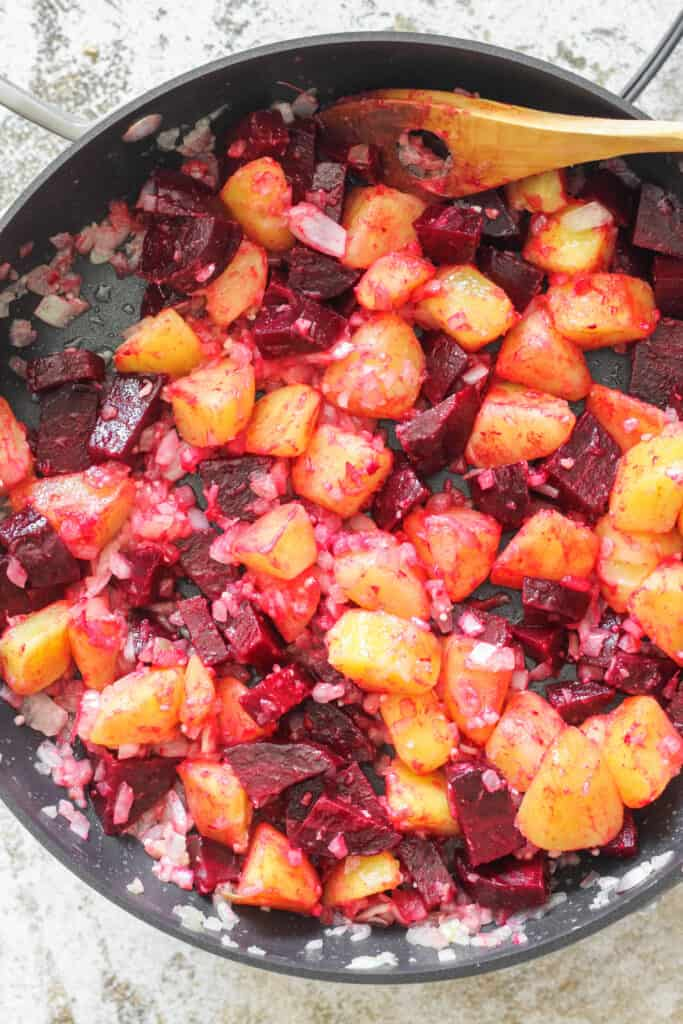 Skillet filled with beets and potatoes