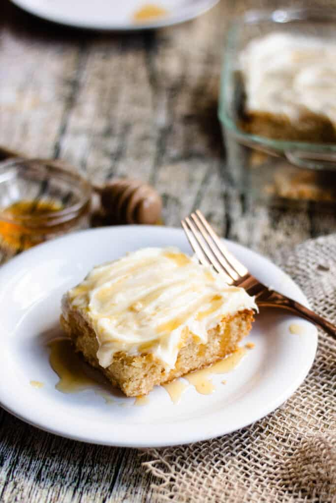 Plated piece of honey cake with a gold fork behind it, dripping with honey