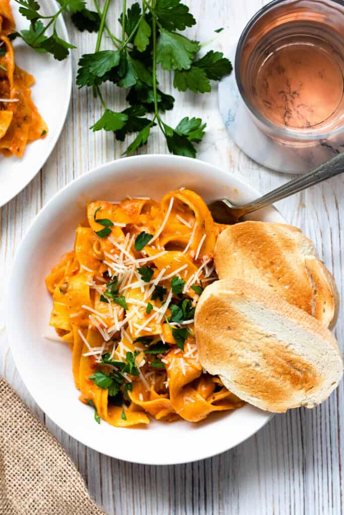 Bowl of pasta with parley, bread and wine surrounding it