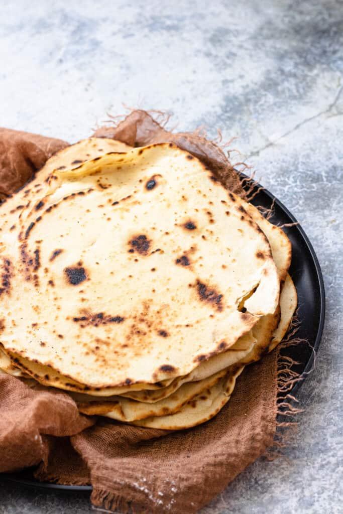 Flour tortillas sitting on a black plate.